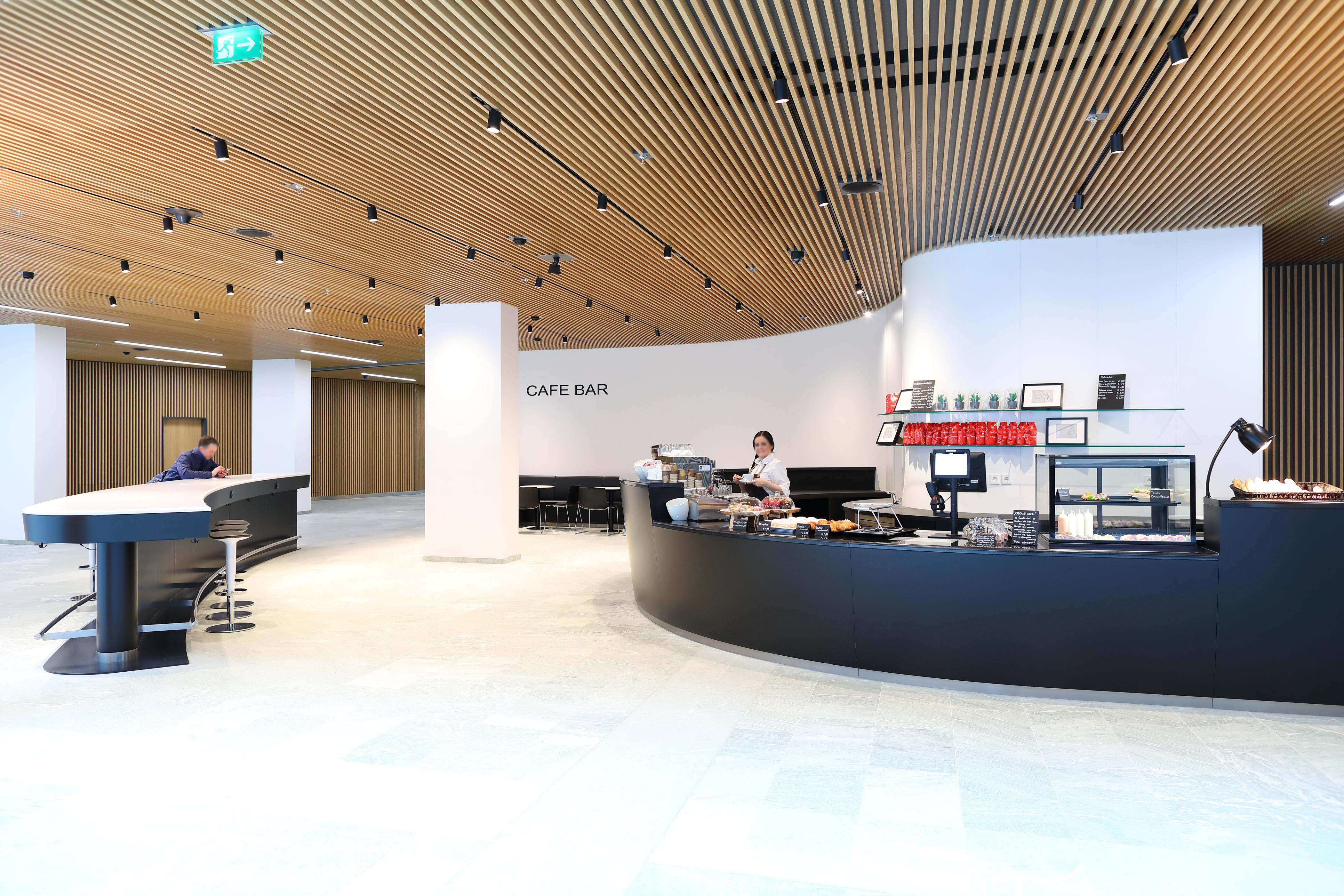 Photo: EURO PLAZA; Restaurant Plaza Eurest; coffee bar, very modern and generously designed, featuring a high curved table; an employee is preparing coffee; a guest with a mobile phone at the table.